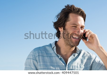 Handsome young man smiling and talking on phone. Cheerful young man in a joyful conversation at telephone with copy space. Portrait of happy joyous man using smart phone outdoor.  - stock photo