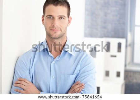 Handsome young man smiling arms crossed.? - stock photo