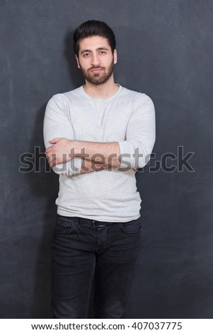 Handsome Young Man Smiling at the Camera Against chalkboard Wall with Copy Space