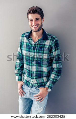 Handsome young man smiling in front of a grey wall - stock photo