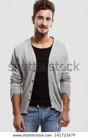 Handsome young man smiling, over a gray background - stock photo