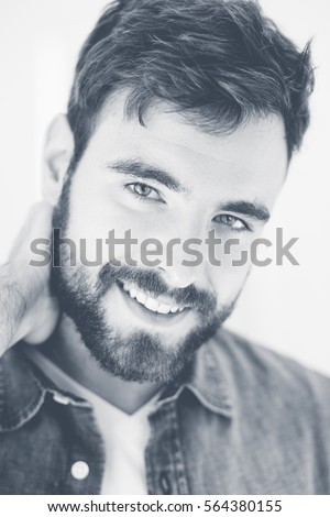 Handsome young man smiling wearing a jeans shirt.