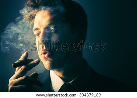 Handsome young man smoking cigar - stock photo