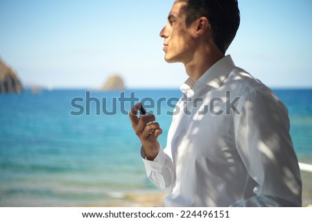 Handsome young man spray perfume. Fashion photo - stock photo