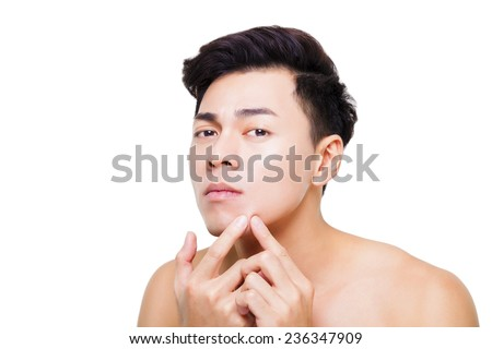 handsome young man Squeezing pimple - stock photo