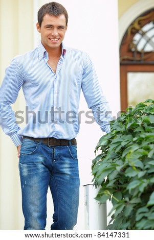 Handsome young man standing in front of his house outdoors