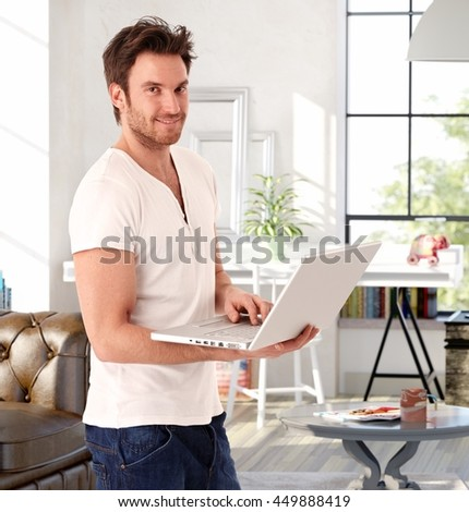 Handsome young man standing in living room at home, holding laptop computer, smiling.