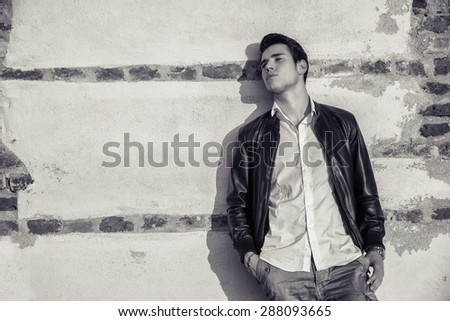 Handsome young man standing in white t-shirt and black leather jacket leaning against old wall behind him, looking away - stock photo