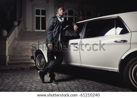 Handsome young man standing next to a limousine - stock photo