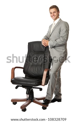 Handsome young man standing next to an armchair, over white background - stock photo