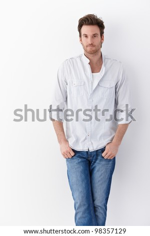 Handsome young man standing over white background, wearing shirt and jeans. - stock photo