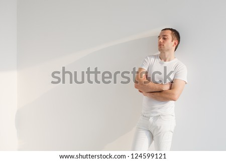 Handsome young man standing , wearing white t-shirt and pants. Studio shot, natural light. - stock photo