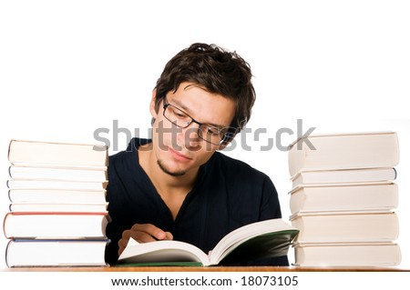 Handsome young man studying and reading between stacks of books on table.