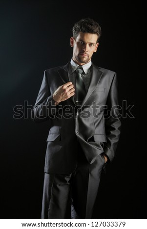 Handsome young man suit casual necklace suit isolated on black - stock photo
