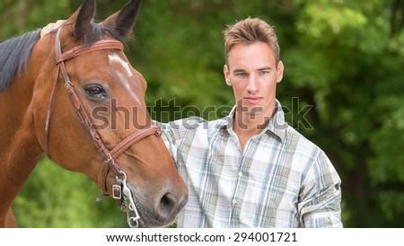 Handsome young man taking care of him brown horse. Soft focus  - stock photo