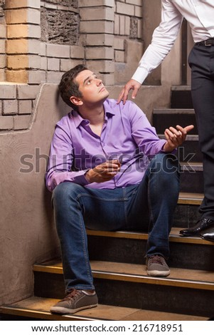 Handsome young man talking to man sitting on stairs. closeup of guy drinking whisky and thinking - stock photo