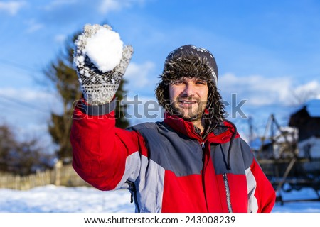 Handsome young man throwing  snowballs in a sunny winter day - stock photo