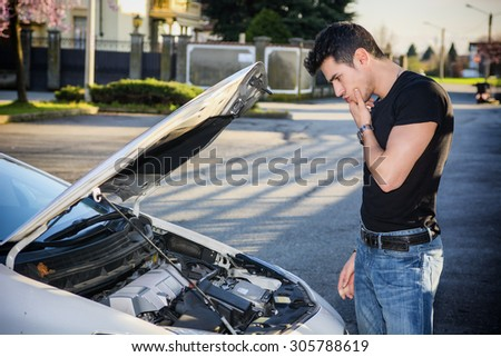 Handsome young man trying to repair a car engine, looking inside open bonnet - stock photo