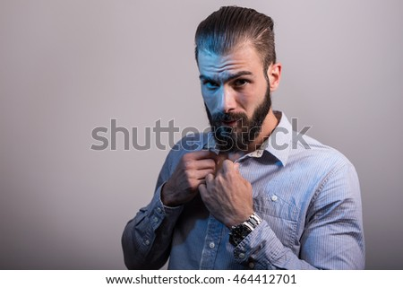 Handsome young man unbuttoning his shirt, studio shoot, depth of field, selective focus , warm tone color filter