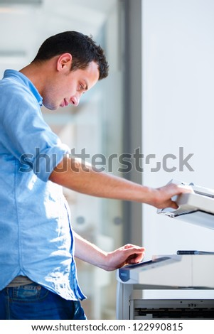 Handsome  young man using a copy machine (shallow DOF; color toned image) - stock photo