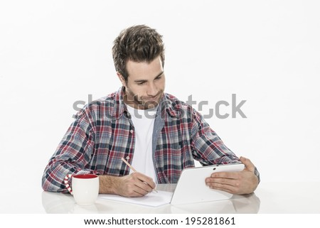 handsome young man using a digital tablet and paper - stock photo