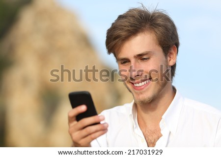 Handsome young man using a mobile phone outdoor with the sky in the background - stock photo