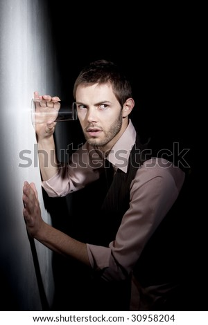 Handsome young man using glass against wall to eavesdrop - stock photo