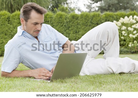 Handsome young man using laptop in park - stock photo