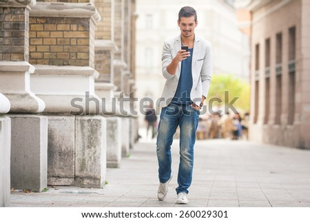 Handsome young man using mobile phone while walking in the city - stock photo