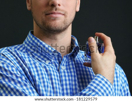 Handsome young man using perfume on black background - stock photo