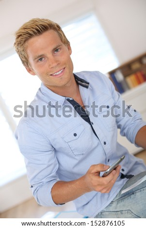 Handsome young man using smartphone in office