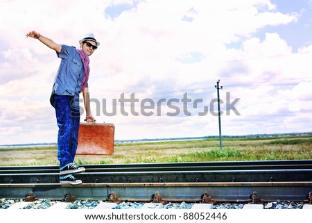 Handsome young man walking along railroad.