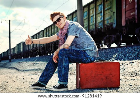 Handsome young man walking along railroad. - stock photo