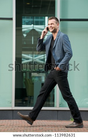 Handsome young man walking and talking on the phone - stock photo