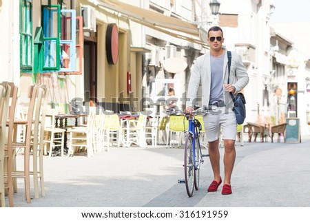 Handsome young man walking down the street with his bicycle beside him - stock photo