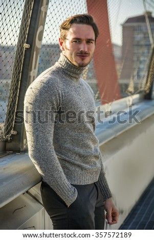 Handsome young man walking in city, wearing winter clothes - stock photo