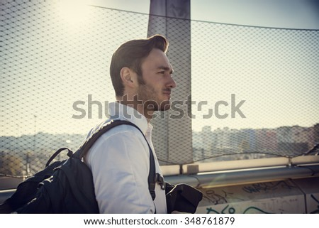 Handsome young man walking in city with backpack on one shoulder, wearing winter clothes - stock photo