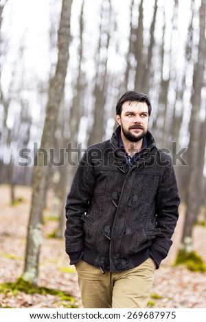 Handsome young man walking in the forest - stock photo