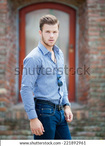 Handsome young man wearing a blue shirt and jeans. Street shooting in Timisoara, Romania