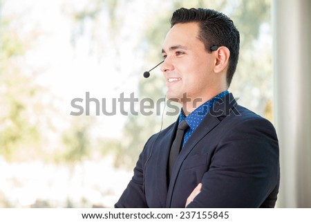 Handsome young man wearing a headset and ready to talk to a customer at a call center - stock photo