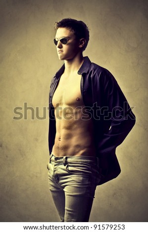 Handsome young man wearing fashion sunglasses - stock photo
