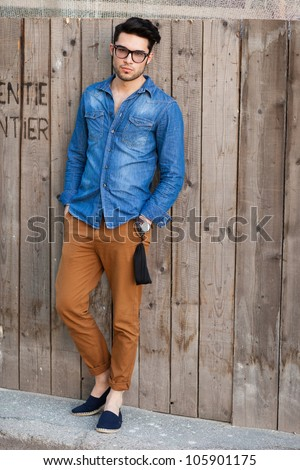 handsome young man wearing glasses posing outdoors - stock photo