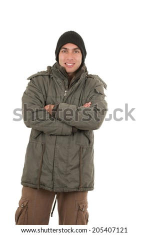 handsome young man wearing green winter coat and a beanie crossing arms isolated on white - stock photo
