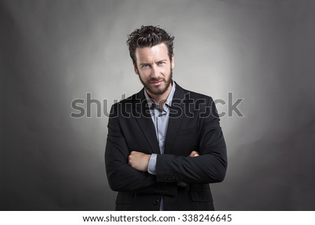 Handsome young man wearing grey suit standing with his arms crossed against grey background.  - stock photo
