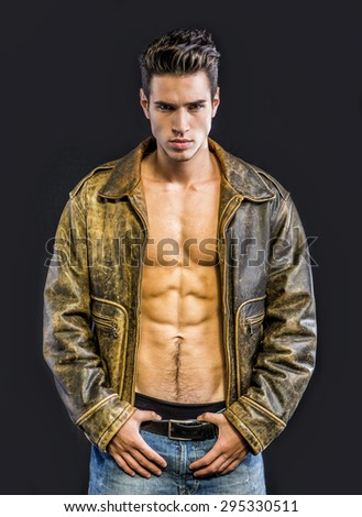 Handsome young man wearing leather jacket on naked torso, isolated on black background looking at camera - stock photo