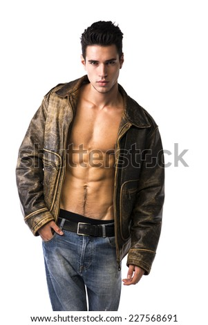 Handsome young man wearing leather jacket on naked torso, isolated on white background looking at camera - stock photo