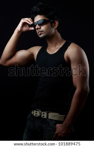 Handsome young man wears sunglasses in a dark background - stock photo