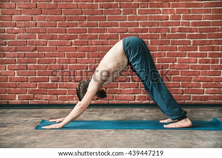 Handsome young man with a beard doing downward dog yoga position on blue matt at wall background, copy space, portrait, adho mukha svanasana. - stock photo