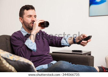 Handsome young man with a beard drinking beer and watching tv at home - stock photo
