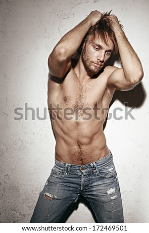 handsome young man with a beard, posing in a studio against a wall
